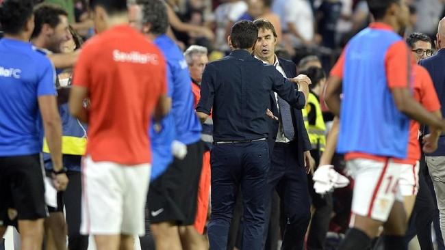 Julen Lopetegui bersalaman dengan pelatih Sevilla Pablo Machin usai pertandingan di Ramon Sanchez Pizjuan, 26 September 2018. Ini adalah kekalahan pertama Real Madrid di La Liga musim ini. (CRISTINA QUICLER / AFP)