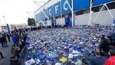 Suporter Leicester City menaruh bunga dan sejumlah barang untuk mengenang pemilik klub Vichai Srivaddhanaprabha yang meninggal dalam kecelakaan helikopter di luar Stadion King Power, Sabtu (27/10) malam waktu setempat. (REUTERS/Peter Nicholls)