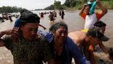 Di sana, para petugas keamanan perbatasan sudah menunggu dengan senapan berisi peluru karet. (Reuters/Carlos Garcia Rawlins)