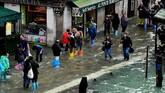 Toko-toko dan restoran setempat tetap digenangi banjir meskipun barikade penahan air pasang telah dipasang di pintu-pintu. (AFP Photo/Miguel Medina)