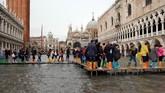 Jalur darurat dari papan kayu dibuat untuk membantu orang-orang bergerak di tengah genangan banjir Venesia. (Reuters/Manuel Silvestri)