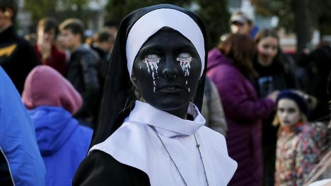 Seseorang berdandan layaknya biarawatijahat dalam sebuah parade Halloween bertajuk 'Zombie Walk' di kota Kiev, Ukraina. (REUTERS/Gleb Garanich)