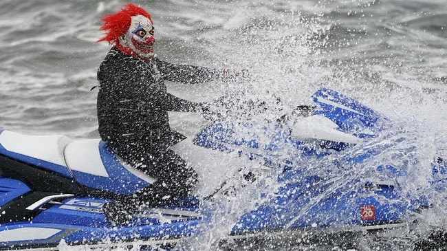 Seorang peserta parade Halloween di East River, New York, Amerika Serikat, berdandan layaknya badut horor sembari menunggangi jet ski. (REUTERS/Carlo Allegri)
