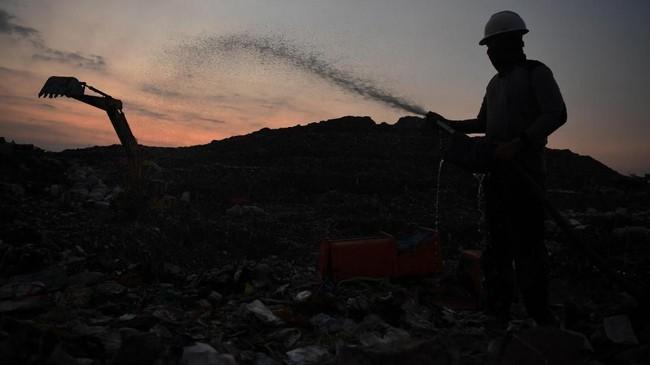 Pekerja menyemprotkan IM6 pada tumpukan sampah untuk menekan bau. (ANTARA FOTO/Zabur Karuru)