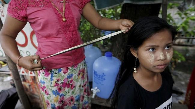 Za Lin pun menyeka air matanya karena rambut panjangnya disir, dipotong di sebuah kios pasar pinggir jalan di Yangon. (REUTERS/Ann Wang)