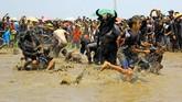 Warga memasuki kubangan yang dijaga kebo-keboan untuk mengambil benih padi yang ditebar. (ANTARA FOTO/Budi Candra)