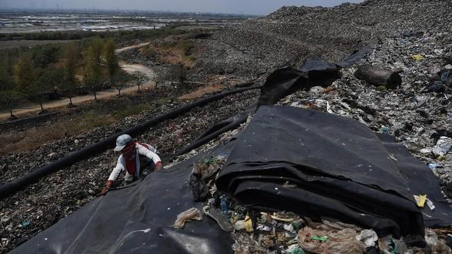 Pekerja terlihat sedang menutupi sampah dengan geomembran agarmemaksimalkan hasil gas metana dan tersalurkan dengan baik melalui pipa menuju sumur gas.(ANTARA FOTO/Zabur Karuru)