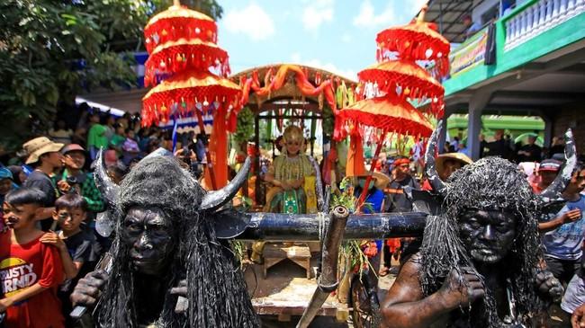 Pemeran kebo-keboan mengarak wanita yang disimbolkan sebagai sosok Dewi Sri (dewi padi) saat digelar ritual adata Kebo-keboan di Alasmalang, Banyuwangi, Jawa Timur. (ANTARA FOTO/Budi Candra)