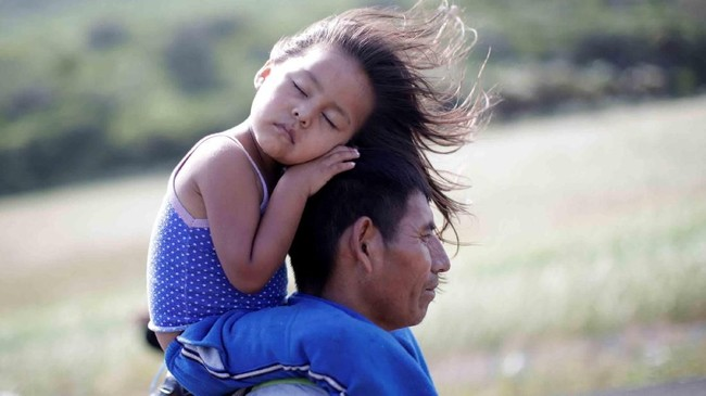 Rosendo Noviega, 38, imigran dari Guatemala, menggendong anaknya Belinda Izabel saat berjalan di Juchitan dari Santiago Niltepec, Meksiko. Ia berasal dari Amerika Tengah, menuju Amerika Serikat. (Reuters/Ueslei Marcelino)