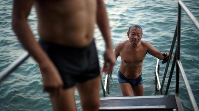 Mereka telah berenang di sana selama beberapa dekade. Mereka terjun ke air laut dari sebuah jembatan kecil dengan latar belakang kapal-kapal kontainer yang sibuk, deretan kapal feri lalu lalang, dan berbagai kapal nelayan.(REUTERS/Hannah McKay)