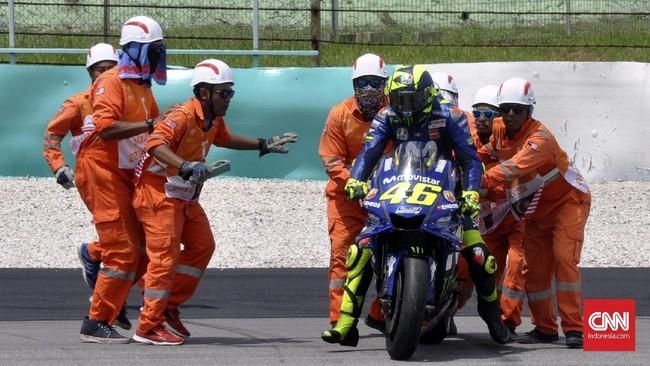 Sejumlah marshal membantu Valentino Rossi yang terjatuh di MotoGP Malaysia 2018. Rossi berusaha bangkit dan kembali balapan namun akhirnya hanya finis di posisi ke-18. (CNN Indonesia/Haryanto Tri Wibowo)