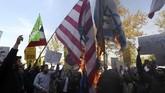 Para demonstran membakar bendera AS, sosok Paman Sam dan foto Presiden Donald Trump di depan bekas Kedutaan Besar AS di Teheran. (AFP Photo/Atta Kenare)