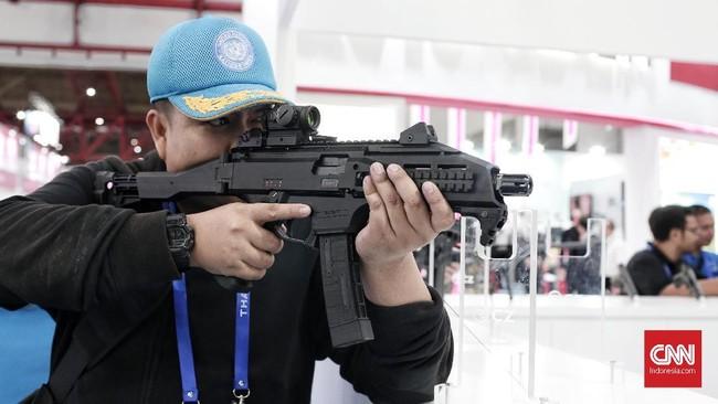 Salah satu pengunjungmencoba senjata taktis buatan Republik Czech pada gelaran Indo Defence 2018, di Kemayoran, Jakarta. (CNN Indonesia/Andry Novelino)