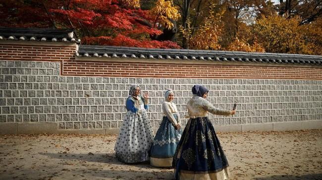 Beberapawisatawan terlihat mengenakan baju tradisional Korea, Hanbok, untuk berswafoto di Istana Gyeongbok, Seoul.