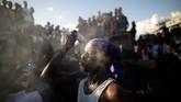 Seorang penganut Voodoo menutupi wajahnya dengan bedak bayu dalam suatu perayaan di pekuburan di Port-au-Prince, Haiti. (REUTERS/Andres Martinez Casares)