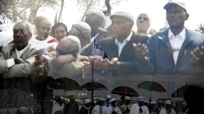 Anggota komunitas Israel-Ethiopia terlihat dari balik panel kaca, sementara bayangan orang-orang lainnya pun terlihat di bagian bawah panel. Mereka berkumpul merayakan hari Sigd yaitu hari raya bagi Yahudi-Ethiopia di Yerusalem. (REUTERS/Amir Cohen)