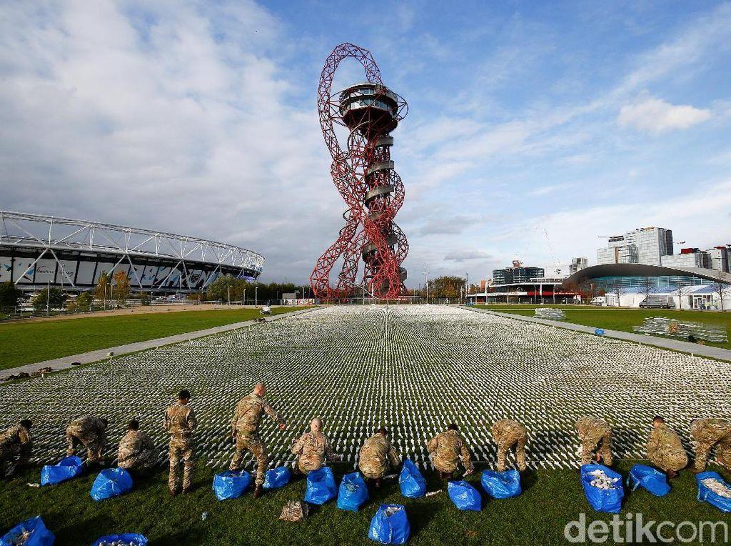 Bersama para tentara Inggris dari Batalyon 1 kerajaan Inggris, Rob memamerkan karyanya di Taman Queen Elizabeth Olympic London, Inggris. REUTERS/Henry Nicholls.