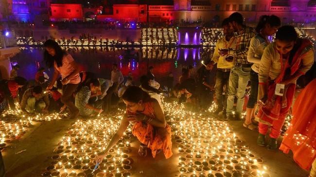 Para wanita India menata letak diya, lampu minyak yang terbuat dari tanah liat, di depan rumah masing-masing untuk merayakan kemenangan Diwali. (AFP PHOTO / NOAH SEELAM)