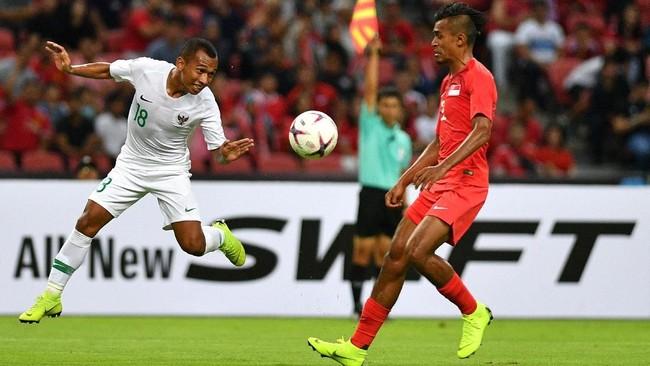 Winger Timnas Indonesia Irfan Jaya (kiri) terkena offsidesaat dibayang-bayangi pemain Singapura Muhammad Shakir Hamzah dalam pertandingan, Jumat (9/11). (ANTARA FOTO/Sigid Kurniawan/pd)