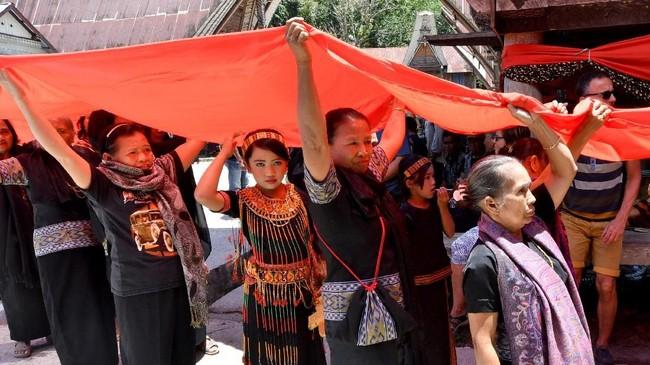 Keluarga membiarkan peti tetap terbuka sebelum dikuburkan. Agar tak mengeluarkan bau, jenazah dimumikan. (AFP/GOH Chai Hin)