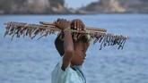 Bocah pedagang asongan berada di pinggir pantai Kawasan Ekonomi Khusus Mandalika di Desa Kuta, Kecamatan Pujut, Praya, Lombok Tengah, NTB.