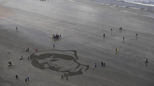 Orang-orang berkumpul di tepi pantai Downhill Beach di Coleraine, Irlandia Utara, 11 November 2018 lalu untuk memperingati seabad usainya Perang Dunia I. (REUTERS/Clodagh Kilcoyne)