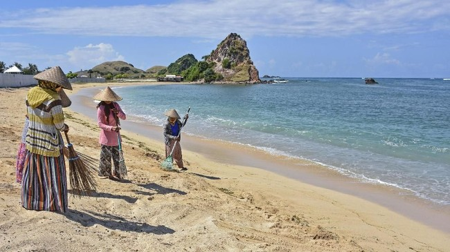 Pekerja membersihkan pantai yang dikelola dan dikembangkan oleh Badan Usaha Milik Negara Indonesia Tourism Development Corporation (ITDC) di Mandalika, Desa Kuta, Kecamatan Pujut, Praya, Lombok Tengah, NTB.