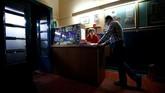 Sang pemilik bioskop Nitsch-Fitz yang berusia 80 tahun, berbincang dengan proyeksionis Wolfgang di meja kasir sementara menunggu calon penonton. (REUTERS/Lisi Niesner)