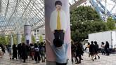 Seorang wanita memeluk foto seorang personel BTS yang ditempel di pilar gedung Tokyo Dome, lokasi konser boyband Korea yang diadakan pada 13 November lalu. (REUTERS/Kim Kyung-Hoon)