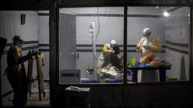 Sejumlah petugas kesehatan diturunkan untuk menangani pasien-pasien Ebola yang belum terkonfirmasi agar penularan tak terus berlanjut.(Photo by John WESSELS/AFP)