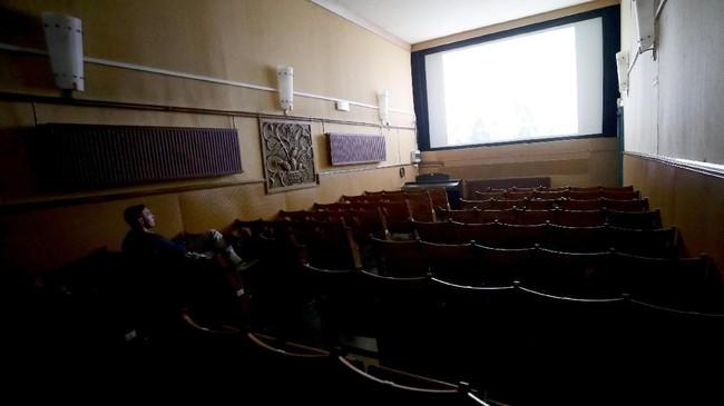 Seorang pecinta film bernama Axel Walde menonton film di Bioskop Breitenseer Lichtspiele yangmerupakan salah satu bioskop tertua di dunia. (REUTERS/Lisi Niesner)