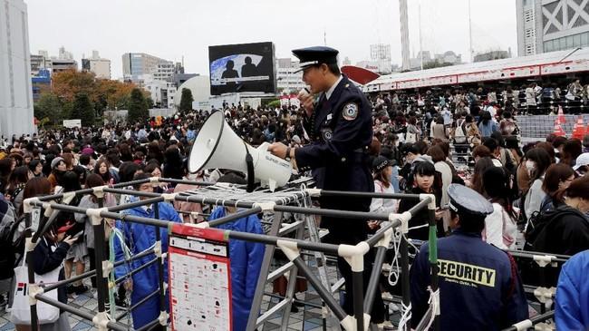 Petugas keamanan dikerahkan untuk menjaga penonton sekaligus mengamankan kondisi di bagian luar lokasi konser BTS di Tokyo, Jepang. (REUTERS/Kim Kyung-Hoon)