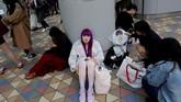 Penggemar yang sudah berdandan habis-habisan duduk menunggu di luar lokasi konser BTS. (REUTERS/Kim Kyung-Hoon)