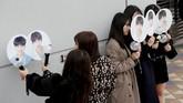 Para penggemar mengambil foto dengan mengangkat semacam kipas bergambar wajah personel BTS. (REUTERS/Kim Kyung-Hoon)