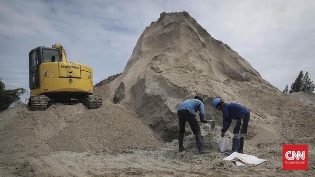 Petugas Suku Dinas Sumber Daya Air (Sudin SDA) Jakarta Utara menyiapkan karung berisi pasir di kawasan Ancol, Pademangan, Jakarta (14/11). (CNN Indonesia/ Hesti Rika)
