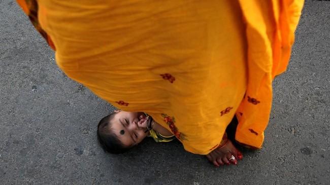 Wanita ini melangkahi seorang bayi mungil, sebuah bagian dari ritual meminta berkat dari Dewa Matahari untuk si bayi di Kolkata, India. (REUTERS/Rupak De Chowdhuri)
