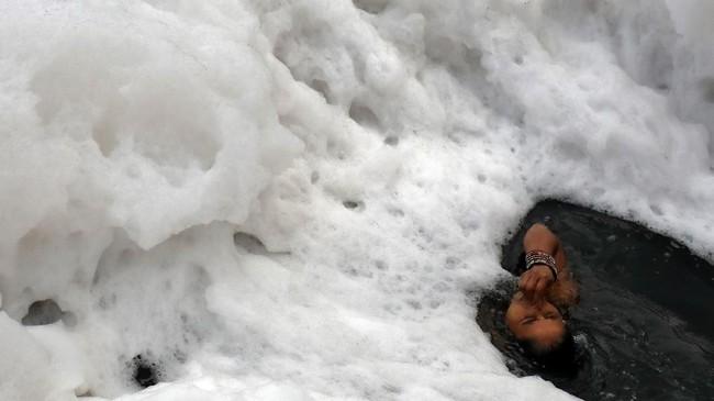 Seorang wanita mencelupkan diri dalam air penuh polusi di sungai Yamuna di New Delhi, India. (REUTERS/Anushree Fadnavis)