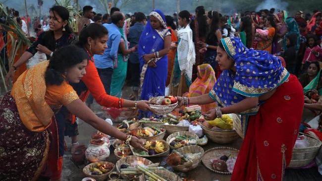 Di India, para pemuja mengumpulkan sajen sebelum memulai penyembahan kepada Dewa Matahari di alur sungai Sabarmati di Ahmedabad. (REUTERS/Amit Dave)