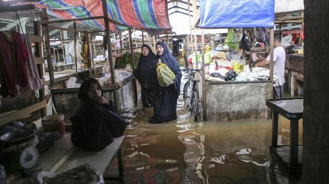 Sejumlah pedagang beraktifitas di lapak dagangnya yang terendam banjir dikawasan Sekip Bendung, Palembang, Sumatera Selatan, Selasa (13/11/2018). ANTARA FOTO/Nova Wahyudi/pd.