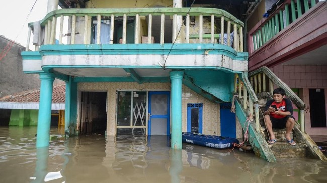 Seorang warga duduk di tangga rumahnya saat banjir yang melanda Kampung Bojong Asih, Dayeuhkolot, Kabupaten Bandung, Senin (12/11/2018). Banjir hingga 1,5 meter tersebut disebabkan oleh luapan Sungai Citarum serta intensitas hujan yang tinggi beberapa hari terakhir di wilayah Kabupaten Bandung. ANTARA FOTO/Raisan Al Farisi/pras.