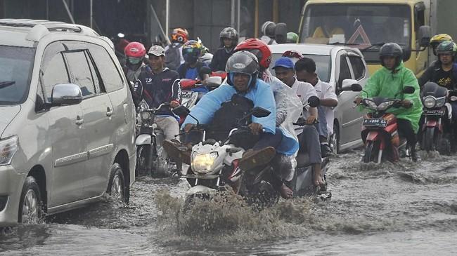 Sejumlah pengendara melintasi banjir di Jalan Sudirman, Serang, Banten, Selasa (13/11/2018). Pihak BMKG merilis peringatan waspada banjir akibat hujan lebat dan cuaca ekstrim yang diprediksi berlangsung hingga 16 November mendatang. ANTARA FOTO/Asep Fathulrahman/ama.