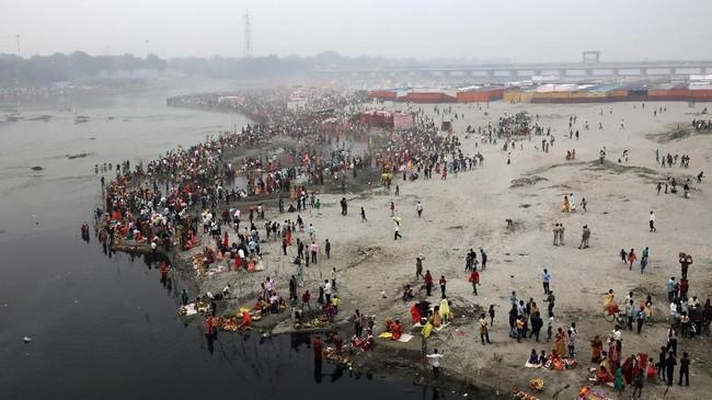 Para pemuja Matahari berkumpul di tepi sungai Yamuna untuk menyembah Matahari di New Delhi, India. (REUTERS/Anushree Fadnavis)