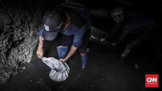 Sisa genangan air banjir biasanya dibersihkan petugas menggunakan pompa, sementara saluran air dikeruk untuk memperlancar arus pembuangan. (CNN Indonesia/ Hesti Rika)