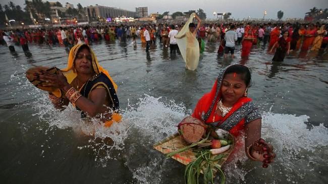 Wanita-wanita Hindu sedang memuja Dewa Matahari, menceburkan diri dalam Laut Arab sebagai bagian dari perayaan Festival Chhath Puja di Mumbai, India.(REUTERS/Francis Mascarenhas)