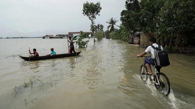 Siswa sekolah melintasi genangan air akibat banjir di Desa Kedungbenda, Nusawungu, Cilacap, Jateng, Selasa (13/11/2018). ANTARA FOTO/Idhad Zakaria/pras.