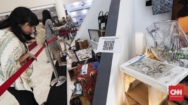 Untuk melihat katalog barang yang dilelang, calon peserta lelang bisa memindai kode batang (barcode) lewat ponsel yang telah disediakan panitia. (CNNIndonesia/Safir Makki).