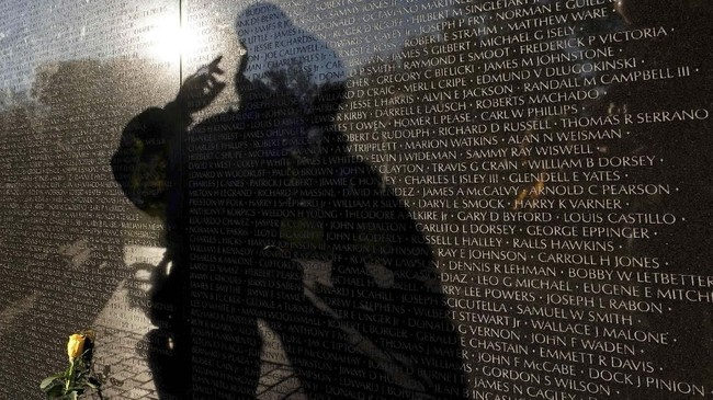 Refleksi seorang pengunjung di tembok Monumen Veteran Vietnam, berisi lebih dari 58 ribu nama tentara Amerika Serikat saat Hari Veteran di Washington, AS. (Reuters/Yuri Gripas)