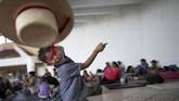 Seorang anak imigran melempar topi di sebuah kamp di Pijijiapan, Meksiko. Ia adalah salah satu yang ikut dalam karavan dari Amerika Tengah yang ingin menuju Amerika Serikat. (Reuters/Ueslei Marcelino)