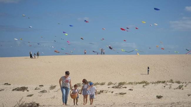 Seorang perempuan berjalan dengan anak-anaknya di tengah Festival Internasional Layang-layang ke-XXXI yang dihadiri sekitar 450 penerbang layang-layang profesional dari seluruh dunia di Pulau Canaria, Spanyol. (AFP/Desiree Martin)
