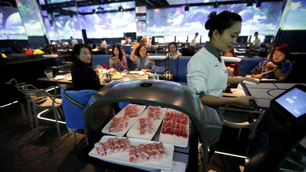 Robot pelayan membawa piring untuk memenuhi pesanan para pengunjung tiba di sebuah meja di restoran Haidilao Beijing, China. Reuters/Jason Lee
